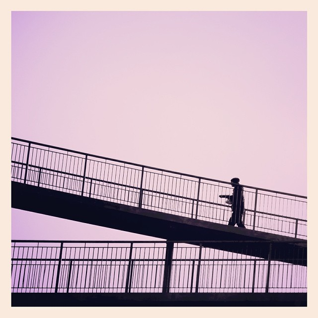 The silhouetted man carrying an unknown object, the bridge and the lilac sky. - iPhone photo by Tony Hammond